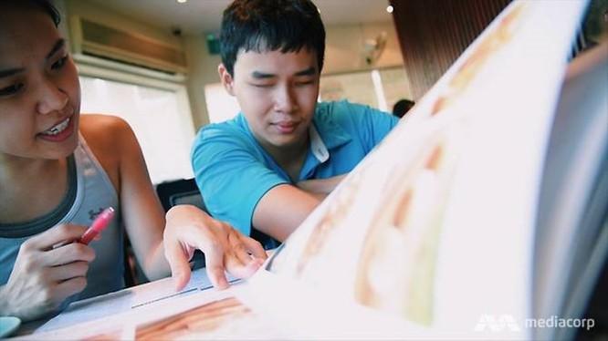 Bạn bè đang giúp anh đọc bản thực đơn trong nhà hàng. Ảnh: ChannelNewsAsia