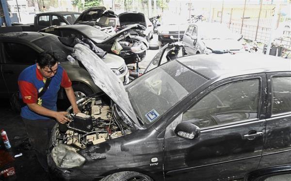 Ông Ng Chee Lun - thợ sửa xe - đang xem xét phần máy của một chiếc xe bị ngâm nước