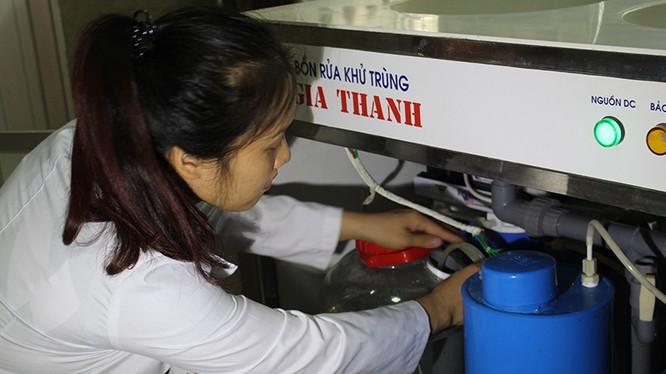 TS Nguyễn Thị Thanh Hải - đồng tác giả Giải pháp hữu ích - bên một thiết bị sản xuất anolit thường dùng trong bệnh viện, trạm y tế, trường học. Ảnh: Phạm Phượng