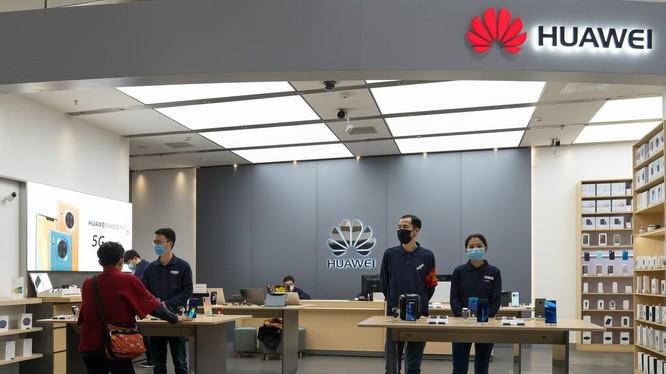 Các nhân viên bán hàng của Huawei đeo khẩu trang tại một cửa hàng của hãng ở Bắc Kinh, Trung Quốc. Ảnh: Business Insider