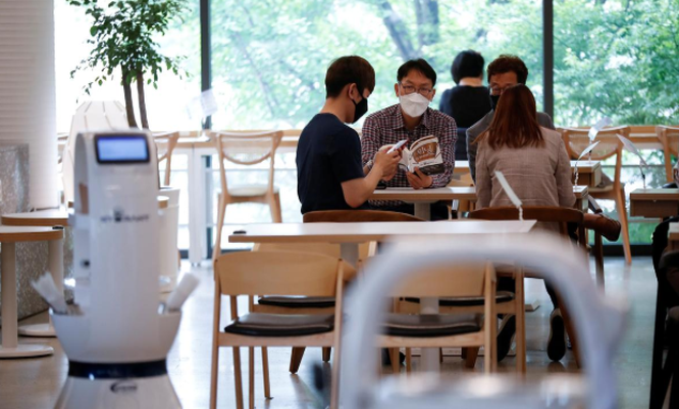 Khách hàng đang chờ đợi phục vụ tại một quán cà phê ở Hàn Quốc nơi robot pha chế sẽ thay thế hoàn toàn cho vai trò của con người. Ảnh: Reuters
