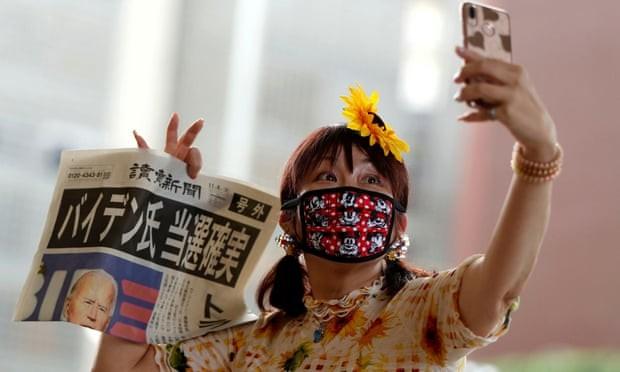 Một phụ nữ Nhật Bản chụp ảnh selfie với tờ báo đưa tin chiến thắng của Biden. (Ảnh: The Guardian)