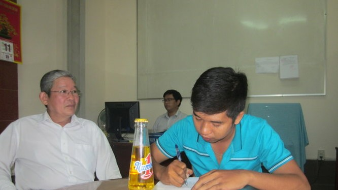 Ông Nguyễn Văn Lợi hướng dẫn anh Định (phải) làm thủ tục khiếu nại - Ảnh: Hoài Thương