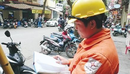 Công nhân Công ty điện lực Hoàn Kiếm đang chốt chỉ số công tơ từng hộ dân trên phố Đường Thành, Hà Nội.