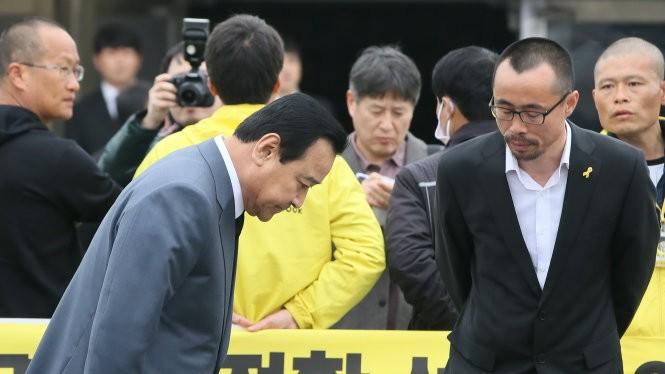 Thủ tướng Hàn Quốc Lee Wan-Koo cúi đầu trong lễ kỷ niệm một năm thảm họa chìm phà Sewol - Ảnh: Reuters