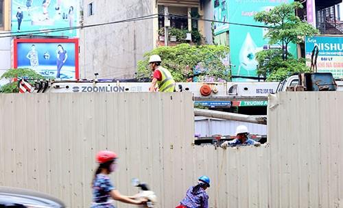 Vết rách ở tường rào do thanh cừ đổ vào sáng nay đang được công nhân bịt lại, chiếc cần cẩu trong công trường cũng được hạ xuống.