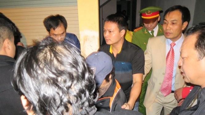 Bà Châu Thị Thu Nga (giữa, chụp mũ) bị bắt giữ và dẫn giải về trại giam vào tối khuya 7-1