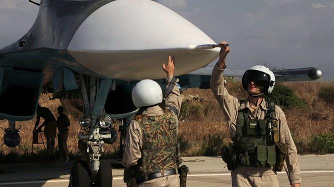 Phi công Su-34 của Nga tại căn cứ không quân gần Latakia, Syria chào mũi máy bay - Ảnh: RIA