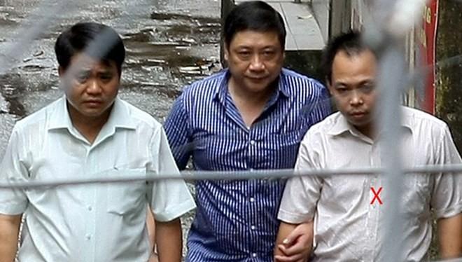 Thiếu tướng Chung (trái) cùng Bình (ngoài cùng bên phải) ra xe về trụ sở công an