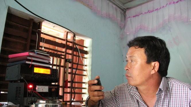 Ông Nguyễn Thanh Nam, người trực icom cộng đồng xã Bình Châu vẫn đang liên lạc với tàu cá QNg 95861 để theo dõi thông tin tàu đang về đất liền - Ảnh: Trần Mai