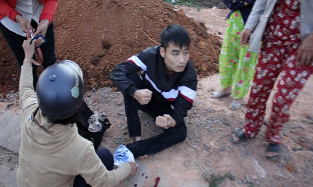 Một nạn nhân tại thị trấn Đắk Hà bị xe điên tông đang ngồi bên vệ đường đợi xe cấp cứu - Ảnh do bạn đọc cung cấp