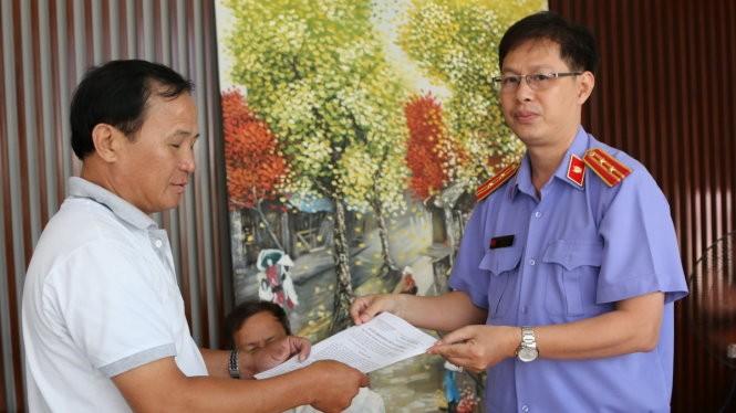 Đại diện VKSND huyện Bình Chánh, TP.HCM trao quyết định đình chỉ vụ án, đình chỉ bị can cho ông Tấn - Ảnh: Gia Minh