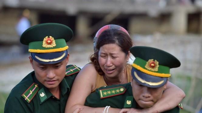 Vợ của nạn nhân Phạm Tấn Cường khóc ngất trong khi được lực lượng biên phòng Đà Nẵng dìu đi - Ảnh: LÊ HẢI SƠN