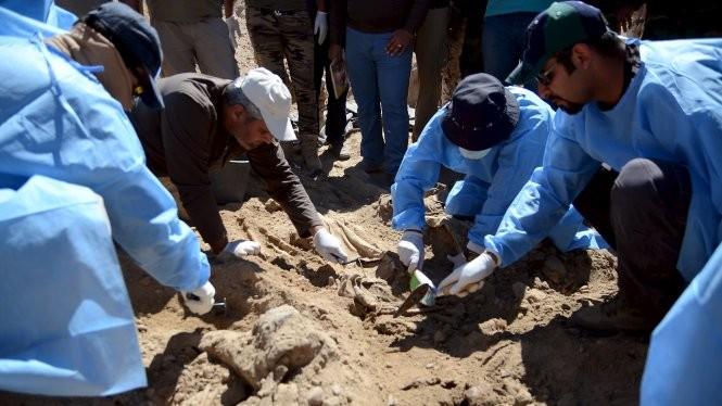 Các chuyên gia pháp y Iraq khai quật một hố chôn tập thể ở Tikrit Ảnh: Reuters