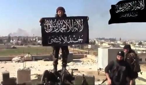 Một tay súng IS giương cờ tại làng Hama. Ảnh: AFP
