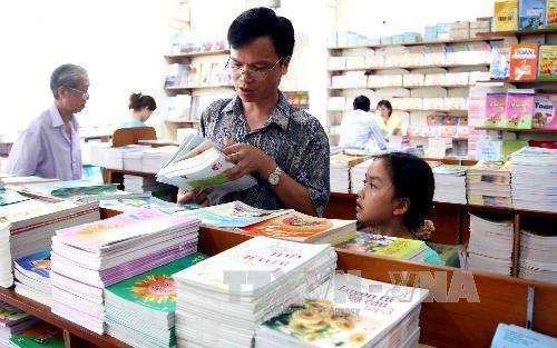 Phụ huynh học sinh chọn mua sách giáo khoa tại siêu thị của công ty ở số 45b Lý Thường Kiệt, quận Hoàn Kiếm, Hà Nội. Ảnh: Quý Trung - TTXVN