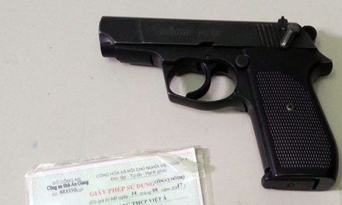 Khẩu súng bắn đạn cao su mà Phó tổng giám đốc sử dụng và giấy phép sử dụng. Ảnh:An Nhơn