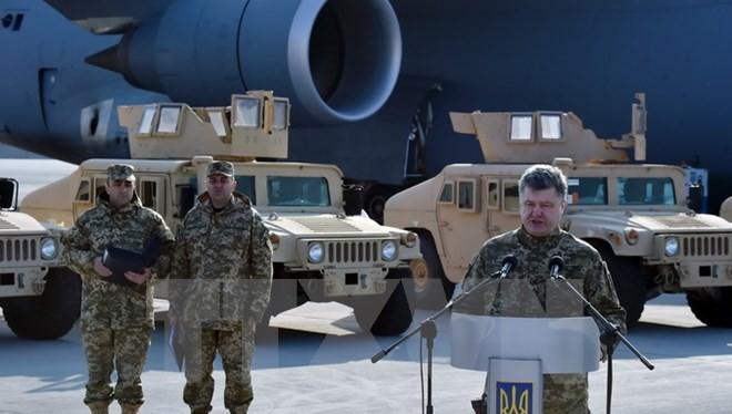 Tổng thống Ukraine Petro Poroshenko (phải) tại lễ tiếp nhận gói viện trợ phi sát thương đầu tiên của Mỹ tại sân bay Kiev ngày 25/3. (Nguồn: AFP/TTXVN)