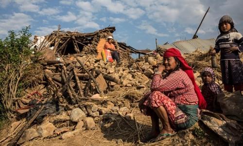 Người dân ngồi trước ngôi nhà bị động đất phá hủy ở Kathmandu. Ảnh: EPA