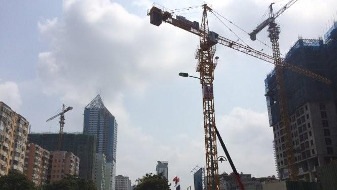 Hàng loạt cần cẩu công trường xây dựng lơ lửng đe dọa an toàn cho người đi đường trên đường Lê Văn Lương (Hà Nội) - Ảnh: Lâm Hoài