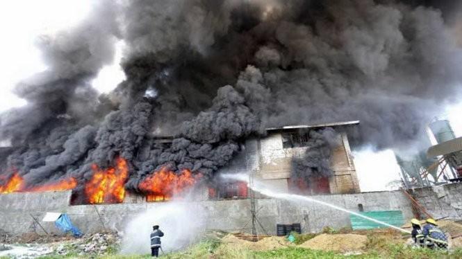 Nhân viên cứu hỏ nỗ lực dập tắt ngọn lửa tại nhà máy ở ngoại ô Valenzuela Ảnh: AFP