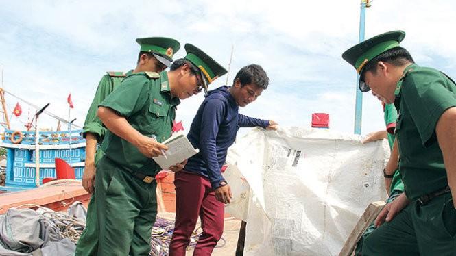 Ngư dân báo cáo với lực lượng biên phòng việc bị tàu Trung Quốc cướp phá - Ảnh: TRẦN MAI