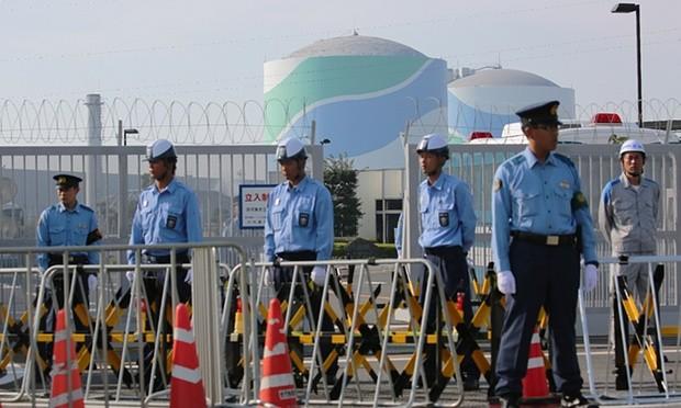Cảnh sát đứng canh gác ngoài khu Tổ hợp hạt nhân Sendai, ngăn chặn người biểu tình phản đối tái khởi động chương trình.