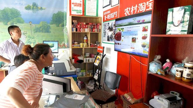 Người dân đến xem mua hàng ở cửa hàng của Alibaba ở thôn Kim Gia, TP Đồng Lư, tỉnh Chiết Giang. Tập đoàn bán lẻ qua mạng cho rằng thị trường nông thôn sẽ đem lại doanh thu đến 74 tỉ USD - Ảnh: Reuters