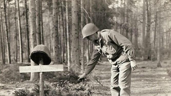 Một lính Mỹ đặt các cành thông lên mộ của lính Mỹ vô danh, bị quân Đức chôn trước khi rút lui.