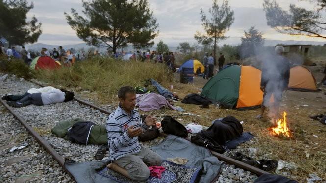 Người nhập cư Syria nghỉ chân ở biên giới Hi Lạp - Macedonia - Ảnh: Reuters