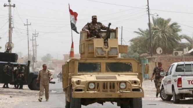 Một binh sỹ thuộc lực lượng an ninh Iraq ở trên chiếc xe quân sự tại thành phố Baiji - Ảnh: Reuters