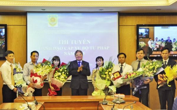 Bộ trưởng Bộ Tư pháp Hà Hùng Cường tặng hoa chúc mừng các ứng viên trúng tuyển. Ảnh: Cổng thông tin Bộ Tư pháp