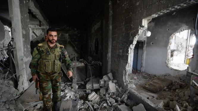 Một binh sĩ Syria chiến đấu trong khu đổ nát của thành phố vệ tinh Darayya