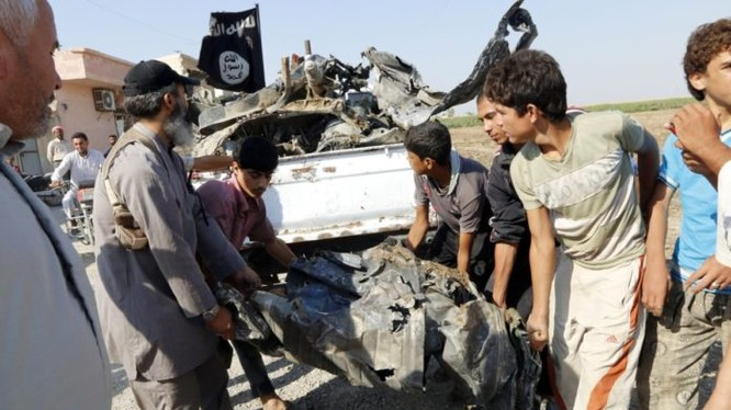 Các tay súng IS thu lượm mảnh xác máy bay quân đội Syria