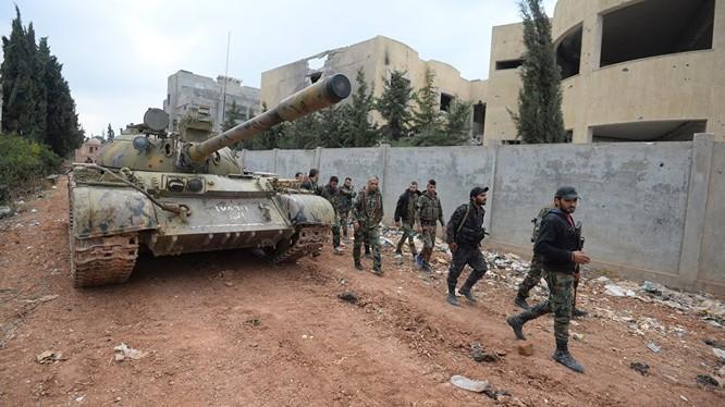 Binh sĩ Syria hành quân trong làng vừa được giải phóng trên miền Bắc tỉnh Hama