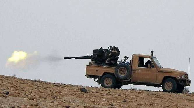 Một binh sĩ Syria đang sử dụng súng máy phòng không trên xe bán tải ở Palmyra