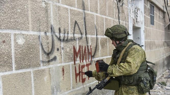 """Một chiến sĩ công binh Nga ghi lên tường dòng chữ """"hết mìn"""""""