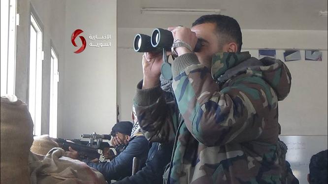 Một sĩ quan Syria đang theo dõi tình hình địch trên chiến trường thành phố Daraa