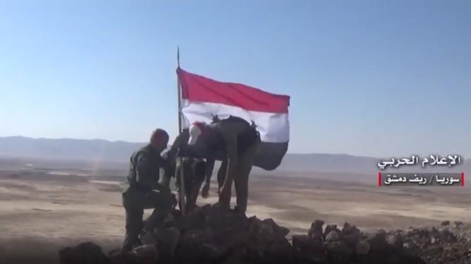 Binh sĩ quân đội Syria cắm cờ trên cao điểm Tal Al-Aabed trên vùng sa mạc phía đông Damascus