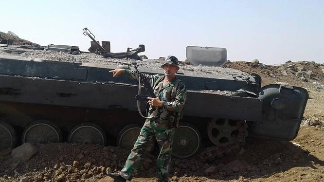 Một binh sĩ lực lượng đặc nhiệm Nga trên chiến trường Hama, bên một xe BMP của phiến quân bị hủy diệt - ảnh Masdar News