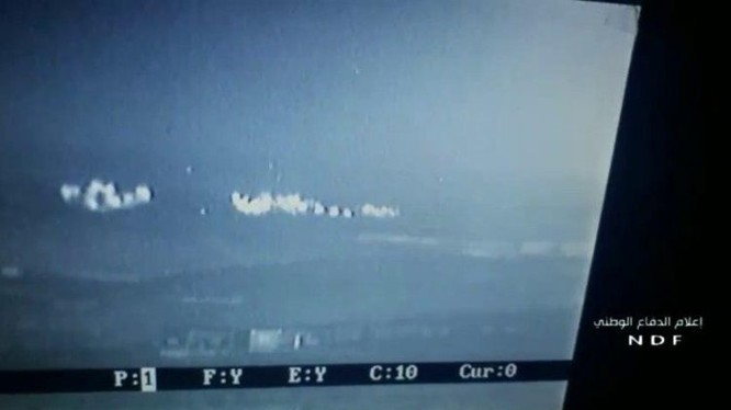 Cảnh pháo phản lực Grad tấn công nhóm chiến binh HTS trên vùng nông thôn Bắc Hama trên màn hinh UAV - ảnh Muraselon