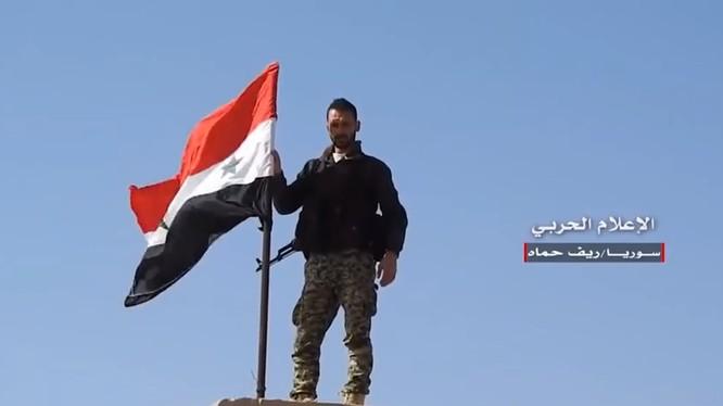 Một binh sĩ Syria thượng cờ trên thị trấn vừa giải phóng. Video truyền thông Hezboaah