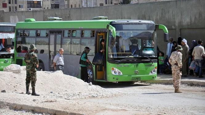 Xe buýt chở các tay súng Hồi giáo cực đoan di tản về Idlib - ảnh Masdar News