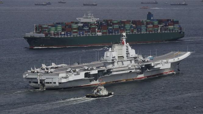 Tàu sân bay Liêu ninh trên nền một chiếc tàu vận tải lớn của Trung Quốc