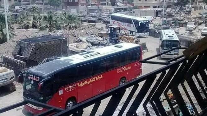 Đoàn xe buýt di tản vào quận Al-Hajar Al-Aswad. Ảnh Masdar News