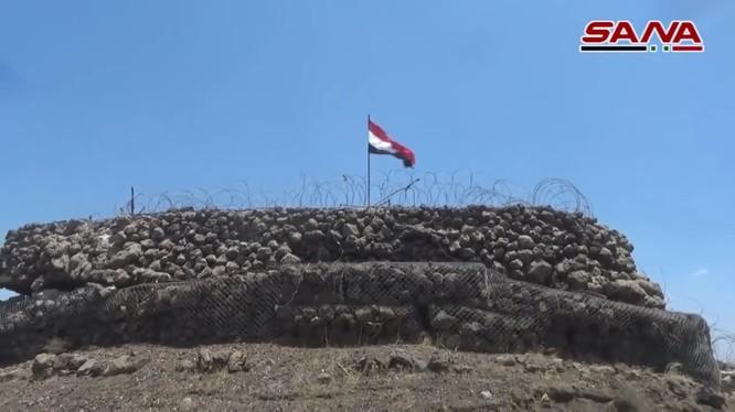 Quân đội Syria thượng cờ trên cao điểm Tal Al-Harrah thuộc vùng nông thôn Daraa. Ảnh video