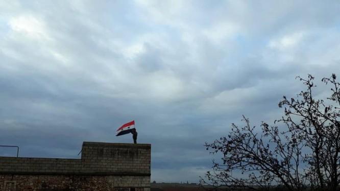 Quân đội Syria thượng cờ trên nóc nhà cao tầng của thành phố Manbij, Aleppo.