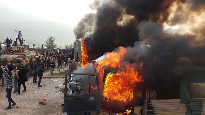 Người Kurd thiêu hủy trang bị của Thổ Nhĩ Kỳ trong căn cứ ở Iraq. Ảnh: NRT.
