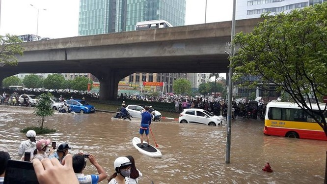 Người dân chèo thuyền trên đường vành đai 3 trong trận mưa ngày 25/5/2016