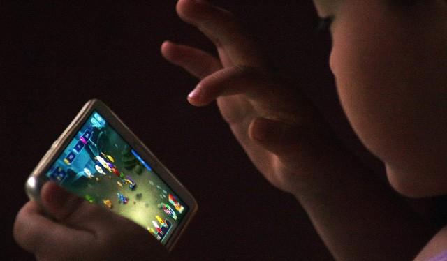 Một em bé đang chơi game online trên thiết bị di động - Ảnh: VCG/VCG
